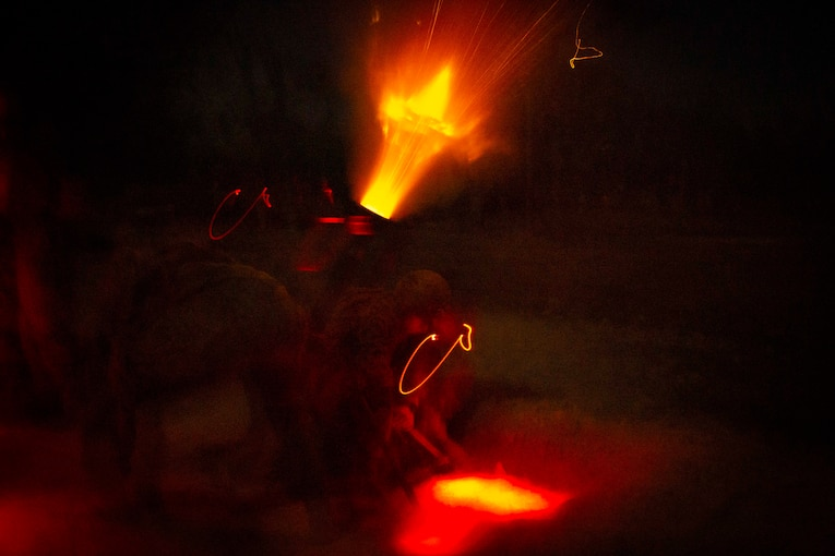 Marines fire a weapon in darkness.