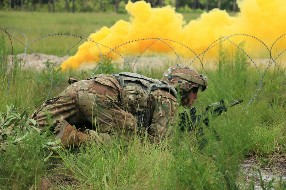 A soldier crawls in grass.
