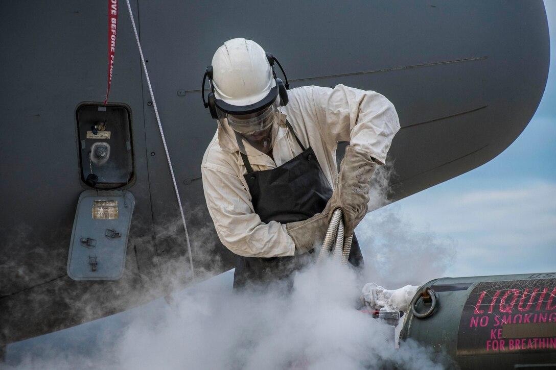 An airman pours liquid oxygen into an aircraft.
