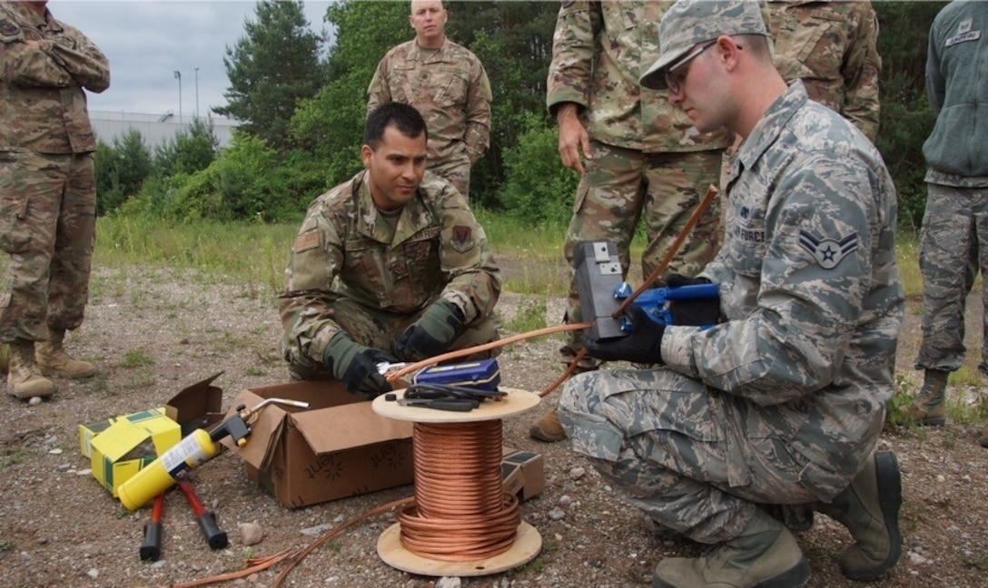 U.S. Air Force Senior Amn. Jorge Lizardi, 235th Air Traffic Controller Squadrons (ATCS) and Airman 1st Class Gabriel Archambault, 260th ATCS receive cad welding training in Ramstein, Germany, June. 4th, 2019. The North Carolina Air National Guard, along with New Hampshire and Maine Air National Guard, flew to Ramstein Air Base, Germany to work with active duty 1st Combat Communications Squadron. The Air National Guard units assisted in training the active duty unit with set-up, use, and tear-down of a mobile tower and deployable tactical air navigation system. (Courtesy Photo by SrA Tsua Yang)