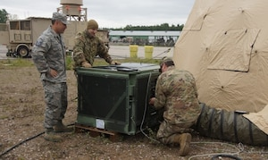 U.S. Air Force Master Sgt. Christopher Philibotte (left), Staff Sgt. James Medeiros (center) and Staff Sgt. Conner Bailey, 260th Air Traffic Controller Squadron, perform maintenance on a field deployable environmental control unit in Ramstein, Germany, June. 6th, 2019. The North Carolina Air National Guard, along with New Hampshire and Maine Air National Guard, flew to Ramstein Air Base, Germany to work with active duty 1st Combat Communications Squadron. The Air National Guard units assisted in training the active duty unit with set-up, use, and tear-down of a mobile tower and deployable tactical air navigation system. (Courtesy Photo by SrA Tsua Yang)