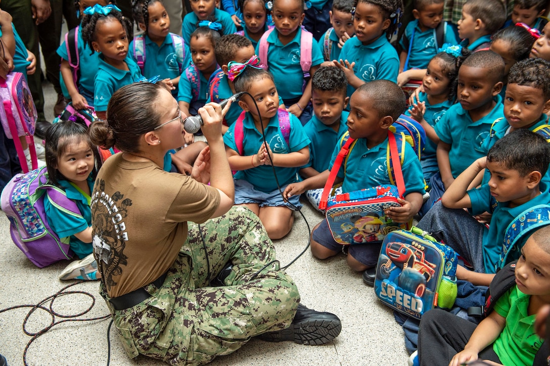 A sailor holding a microphone sits cross-legged on a floor with children and sings to them.