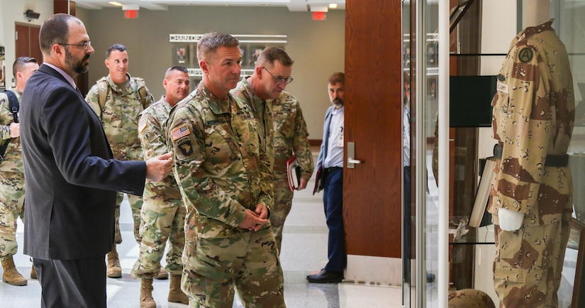 Mr. Michael Clauss (left), U.S. Army Central historian, gives Gen. James McConville (center), U.S. Army Chief of Staff, a brief history tour of Patton Hall, USARCENT's headquarters, on Shaw Air Force Base, S.C., Aug. 1, 2019. Pictured is a memorial dedicated to the late Lt. Gen. John Yeosock, former commanding general of USARCENT during Operation Desert Shield and Operation Desert Storm.