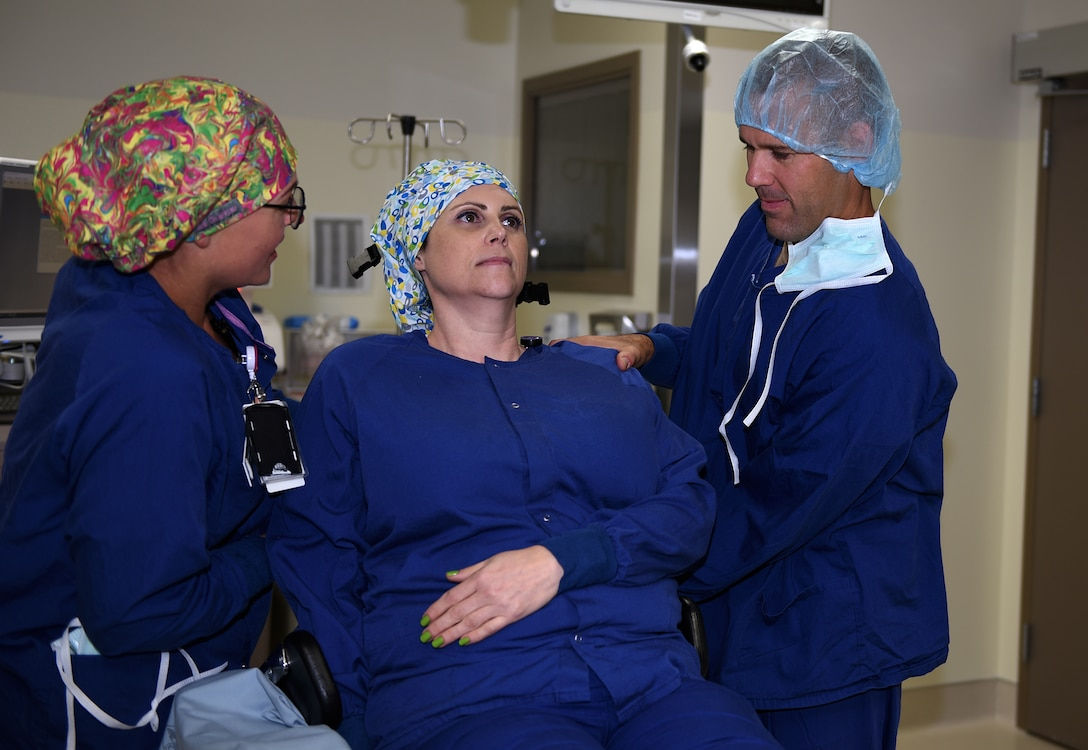 U.S. Air Force Col. Zachery Jiron, right, 60th Air Mobility Wing vice commander, and 1st Lt. Shawna Larson, 60th Surgical Operations Squadron operating room nurse, raise Kirsten Schultz, 60th SCGS operating room nurse, into a sitting position for simulated shoulder surgery Aug. 8, 2019, at David Grant USAF Medical Center Travis Air Force Base, California.  As part of the Leadership Rounds program, Jiron participated in a simulated surgery to get a firsthand experience of all the precautions medical staff take before every surgery. (U.S. Air Force photo by Airman 1st Class Cameron Otte)