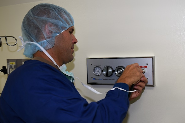 U.S. Air Force Col. Zachery Jiron, 60th Air Mobility Wing vice commander, plugs in the Spider into the pneumatic system to power the Spider's shoulder positioner Aug. 8, 2019, at David Grant USAF Medical Center Travis Air Force Base, California. The Spider is an operating room piece of equipment that is ideal for the traction of ankle, wrist and elbow procedures. As part of the Leadership Rounds program, Jiron participated in a simulated surgery to get a firsthand experience of all the precautions medical staff take before every surgery. (U.S. Air Force photo by Airman 1st Class Cameron Otte)