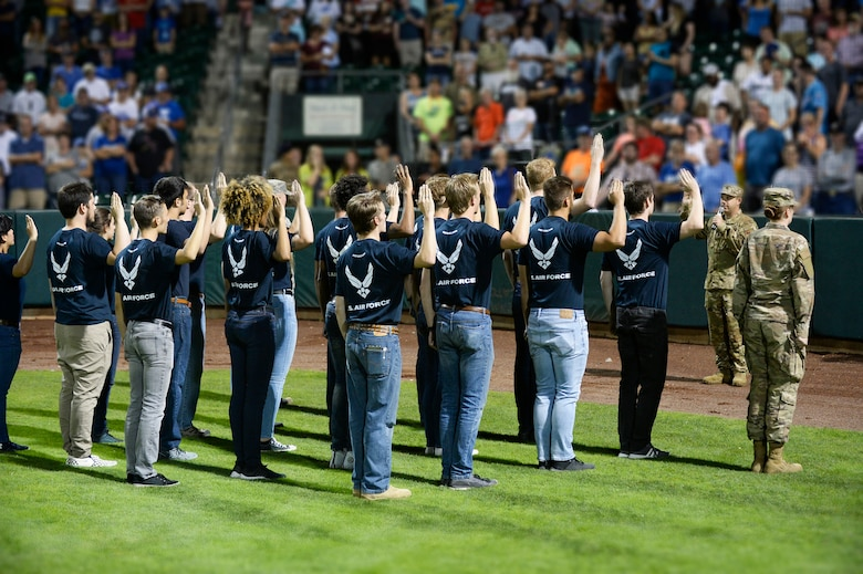 Lt. Col. Jason Haney, 368th Recruiting Squadron commander, gives the oath of enlistment to 22 Air Force recruits during the Aug. 9, 2019, Military Appreciation Night with the Ogden Raptors and Idaho Falls Chuckars at Lindquist Field in Ogden, Utah. Each year, the Raptors and Top of Utah Military Affairs Committee offer tickets to Hill Air Force Base personnel and their families. (U.S. Air Force photo by David Perry)