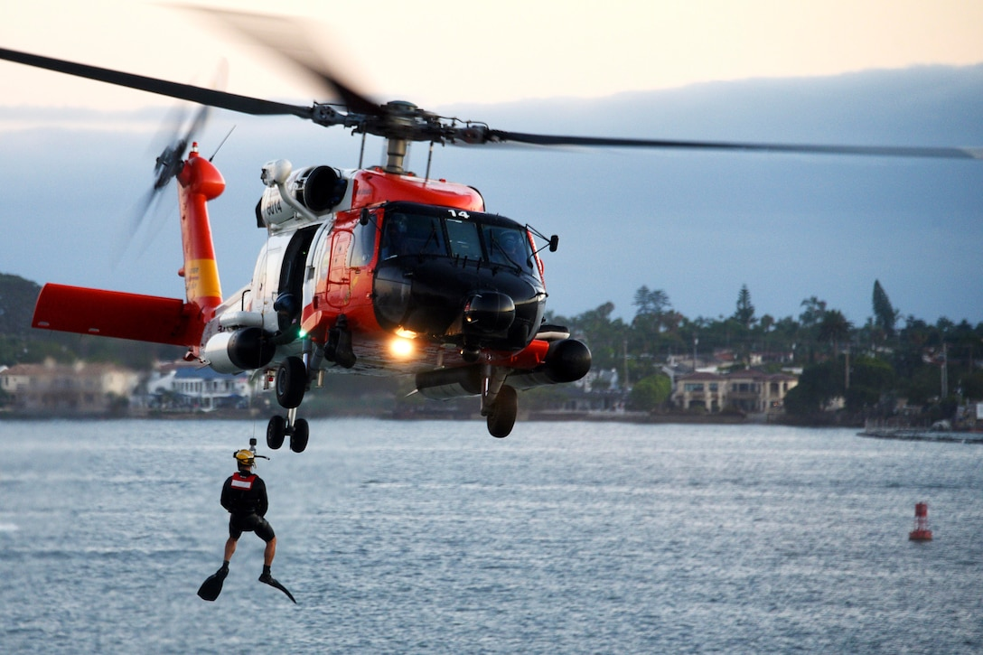 A Coast Guardsman hangs from a helicopter in the air.