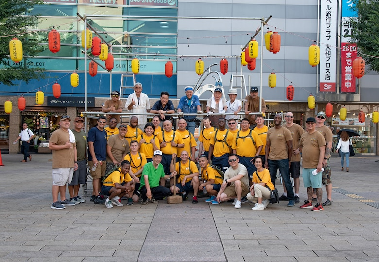 YAMATO, Japan (Aug. 09, 2019) Chief Petty Officers (CPO), CPO selectees and citizens from Yamato city pose for a group photo in front of the Yagura stage they assembled for the city's annual Yamato Furusato summer festival. The festival featured dance routines performed by members of the local community as well as Naval Air Facility Atsugi's Bon Odori dancers.