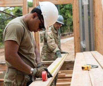U.S. Army Pfc. Jesse Velez, a plumber assigned to the 1156th Engineer Company, 204th Engineer Battalion, New York Army National Guard, measures a board before cutting it during an Innovative Readiness Training (IRT) mission at Camp Paumalu, Haleiwa, Hawaii, July 31, 2019.Engineers from the Air Force, Air National Guard, and the Marine Corps have been working at the camp since May to help build a Science, Technology, Engineering, and Math (STEM) activity center.