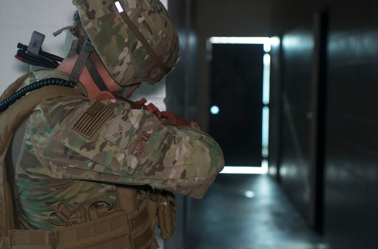 U.S. Air Force Senior Airman Weston Super, a 6th Security Forces Squadron entry controller, aims his training weapon down a hallway during an active shooter exercise at MacDill Air Force Base, Fla., Aug. 8, 2019.