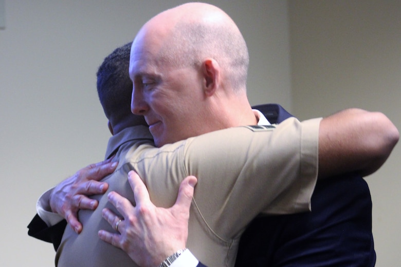 U.S. Marine Cpl. Stewart Rembert, a motor vehicle technician with Combat Logistics Battalion 8, Combat Logistics Regiment 2, 2nd Marine Logistics Group embraces FBI Special Agent Troy Sowers during the agent's retirement ceremony at the FBI Field Office in Knoxville, Tenn., Aug. 9, 2019. Sowers rescued days-old Rembert from a kidnapping in 1997 in Tacoma, Wash.