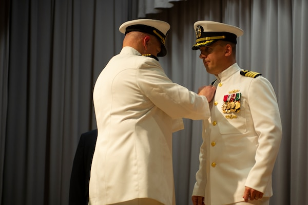 Capt. Brian D. Lawrence, left, pins the Supervisor of Shipbuilding Gulf Coast command pin to the uniform of Capt. Nathan A. Schneider. Schneider assumed command of SSGC during a change of command ceremony Aug. 12.