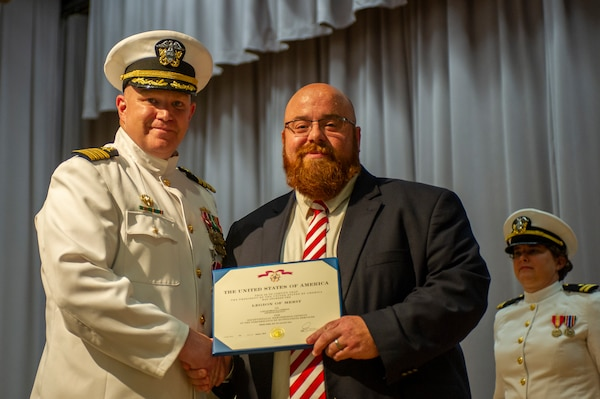 Capt. Brian D. Lawrence, left, accepts a Legion of Merit award from Mr. Mathew Sermon, Executive Director of the Amphibious, Auxiliary and Sealift Office during the Supervisor of Shipbuilding Gulf Coast change of command ceremony Aug. 12.