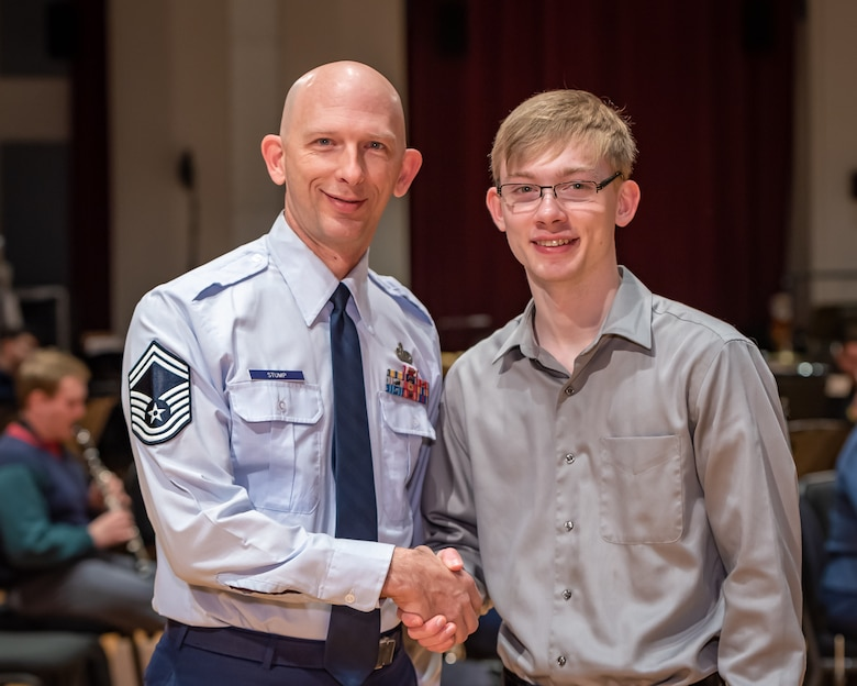 U.S. Air Force Band clarinetist, Senior Master Sgt. David Stump, shakes hands with his son, Andrew Stump, during a rehearsal break on Joint Base Anacostia-Bolling. The rehearsal was part of the 2019 Collegiate Symposium, and it afforded the father and son a unique opportunity to perform together on Saturday, Feb. 4, 2019, at the Rachel M. Schlesinger Concert Hall and Arts Center in Alexandria, Virginia. (U.S. Air Force Photo by MSgt Brandon Chaney)