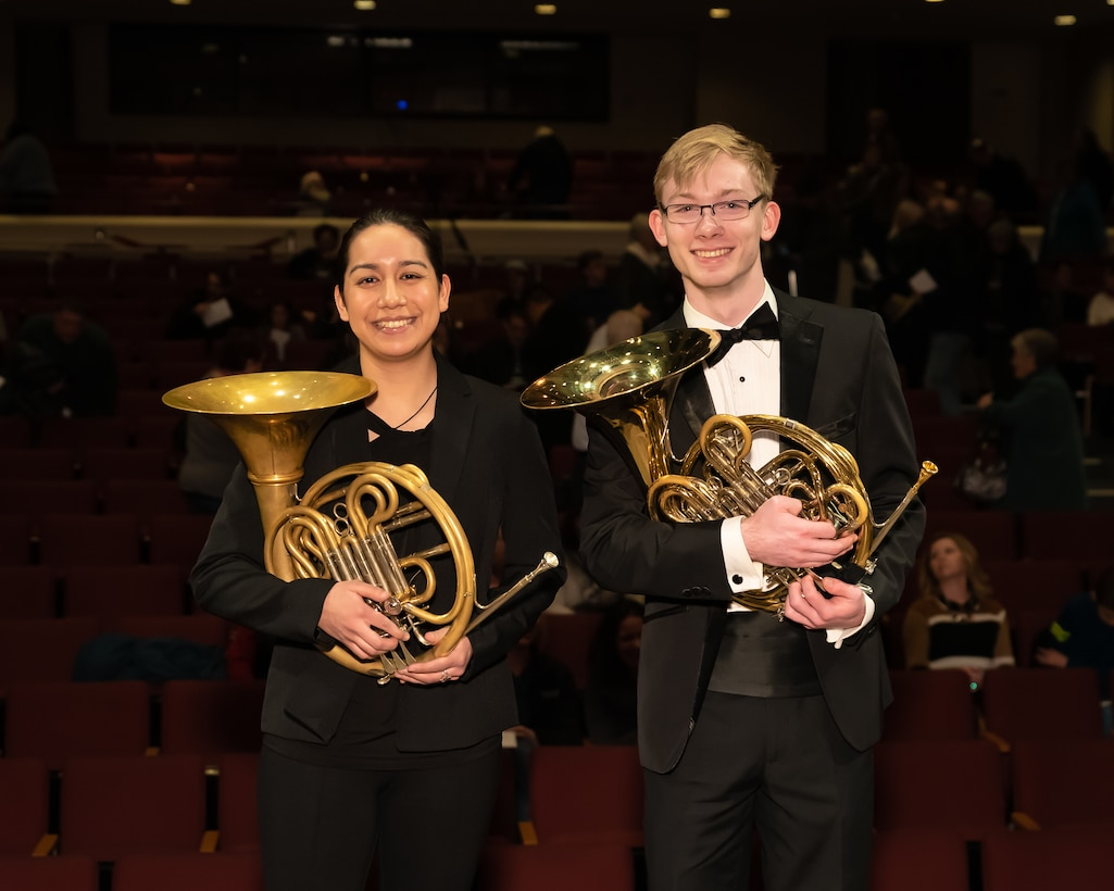Andrew Stump (right) poses with another French hornist on stage prior to the closing concert of The U.S. Air Force Band's 2019 Collegiate Symposium at the Rachel M. Schlesinger Concert Hall and Arts Center in Alexandria, Virginia. Stump, son of U.S. Air Force Band clarinetist Senior Master Sgt. David Stump, had the privilege of performing with the U.S. Air Force Concert Band as part of the symposium. (U.S. Air Force Photo by MSgt Brandon Chaney)