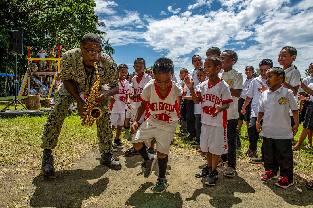 A child dances as a Navy saxophonist performs on a playground and children in matching uniforms watch.