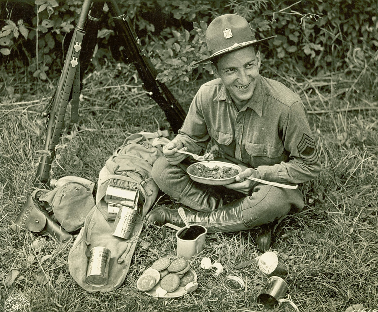 A soldier sits on the ground eating C-rations.
