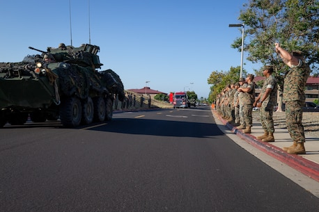 """U.S. Marines with 1st Light Armored Reconnaissance (LAR) Battalion, 1st Marine Division, line the streets to give the Highlander salute during the arrival of the 1st LAR monument at Camp Pendleton, Calif., July 24, 2019. The 1st LAR Marines were nicknamed the """"Highlanders"""" in honor of the famous Scottish Soldiers of the past. The monument was donated by the 1st LAR Association in honor of their fallen brothers and proudly escorted by Marines with 1st LAR. (U.S. Marine photo by Sgt. Tayler P. Schwamb)"""