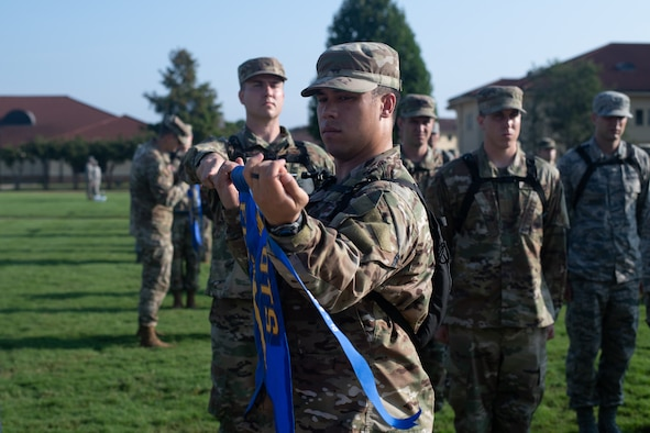 An officer trainee puts his flight's newly earned pennant on their guide-on, Aug. 9, 2019, on Maxwell Air Force Base, Alabama. The pennant ceremony marked the end of the classes second week of training. (U.S. Air Force photo by Airman 1st Class Charles Welty)