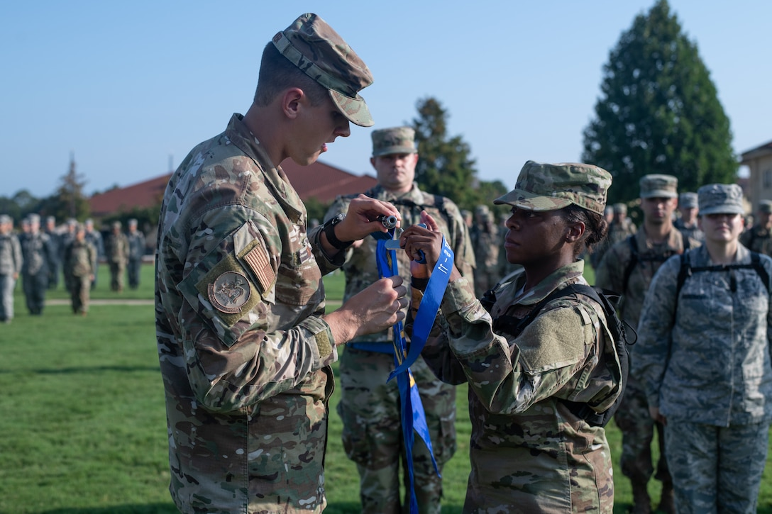 An Air Force Officer Training School flight chief assists his flight in the assembly of their newly earned pennant, Aug. 9, 2019, on Maxwell Air Force Base, Alabama. Officer Training School's class 19-07 is comprised of more than 800 officer trainees and is more than twice the size of an average class at OTS. (U.S. Air Force photo by Airman 1st Class Charles Welty)