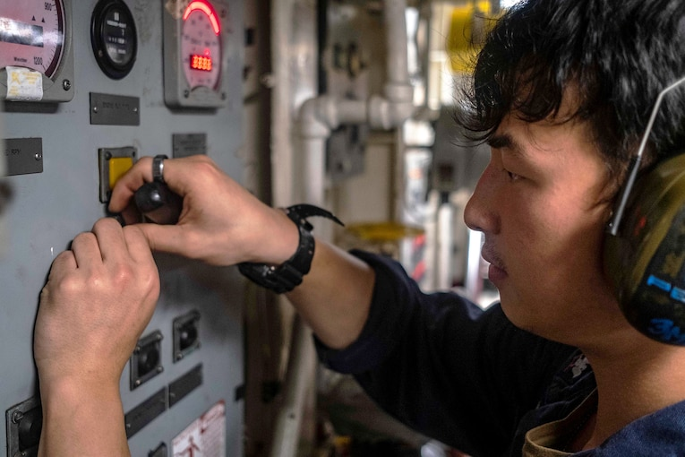 A sailor fixes a control panel.