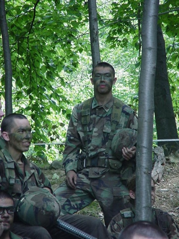 Army cadet stands alongside his fellow cadets during a field training exercise in a forested area.