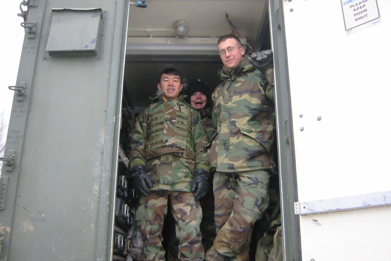 Army officers pose for a photo in the doorway of a building during a cold-weather exercise.