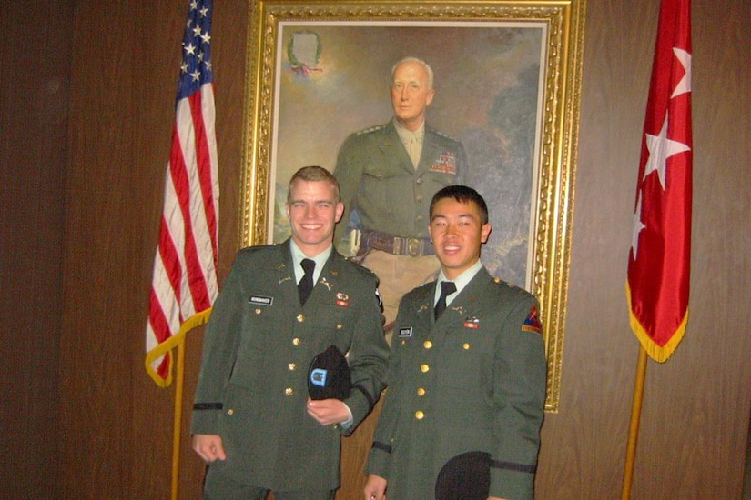 Two Army cadets pose for a photo in front of historic West Point art in their green service uniforms.