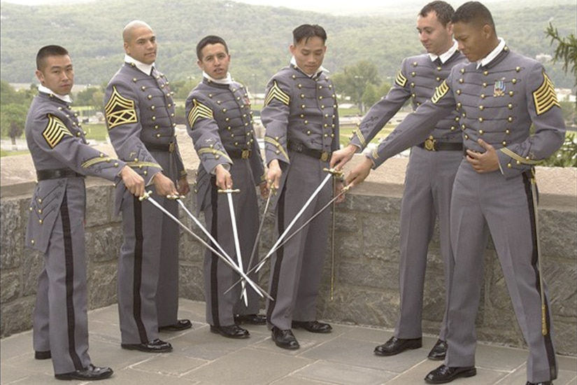 Army cadets pose in a half circle with their swords drawn in their graduation uniforms.
