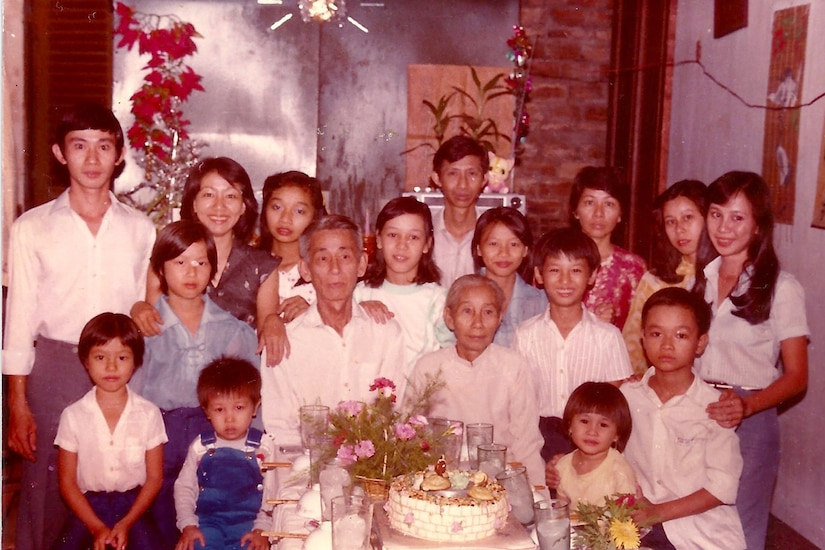 Family poses around a table for a family photo.