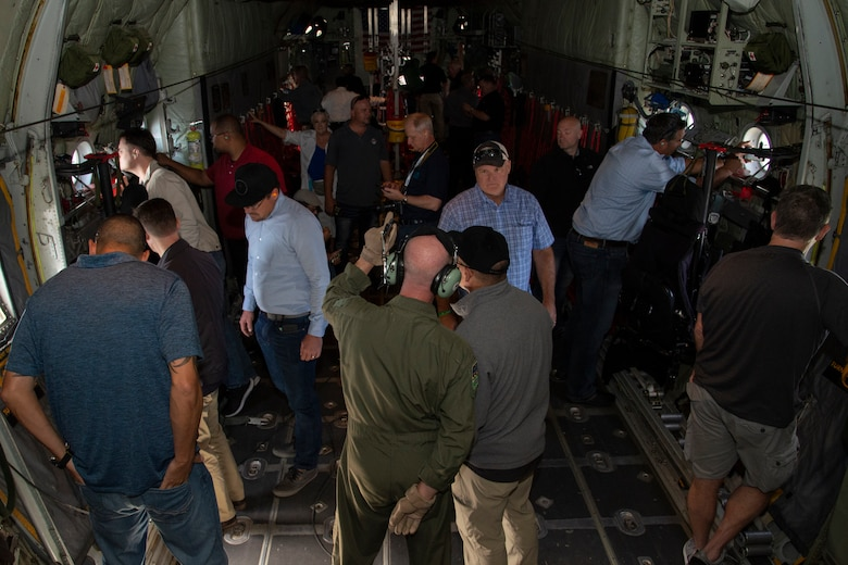 Civilian employers take photos aboard a C-130 Hercules aircraft during training flight near Peterson Air Force Base, Colo., Aug. 9, 2019.