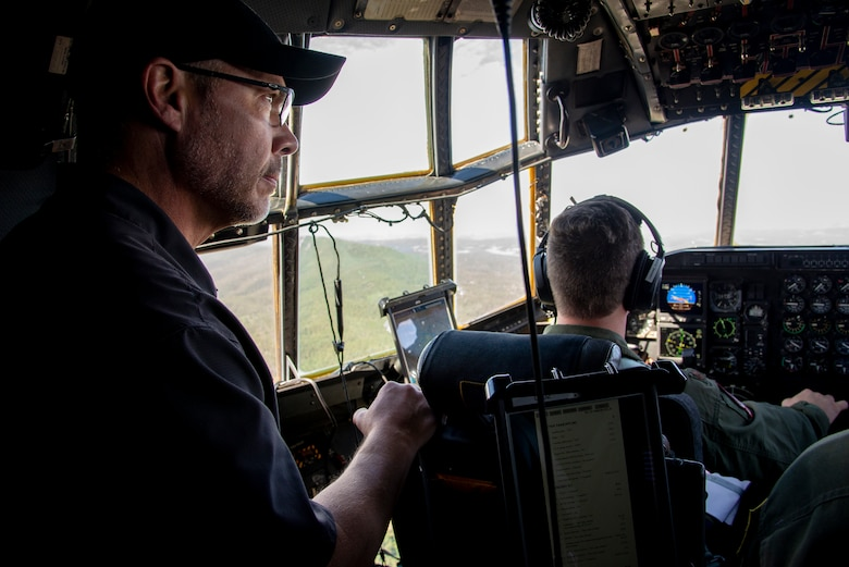 Tim Kulin, a civilian employer to one of the 302nd Airlift Wing's Reserve Citizen Airmen, looks out the window inside the flight deck of a C-130 Hercules aircraft during a training flight, August 9, 2019.