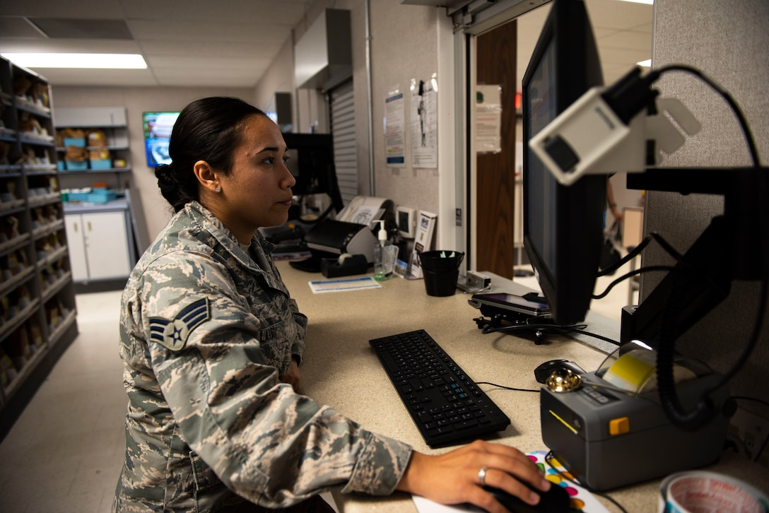 U.S. Air Force Senior Airman Alexandria Lara, 60th Diagnostics and Therapeutic Squadron pharmacy technician, searches customer information on a computer Aug. 12, 2019, at Travis Air Force Base, California. Lara works in the base exchange satellite pharmacy, where the team of seven refills 700 prescriptions a day.  (U.S. Air Force photo by Senior Airman Jonathon Carnell)
