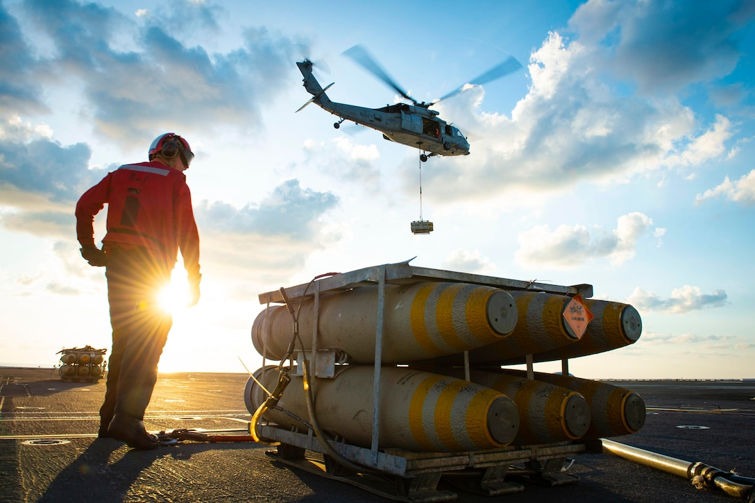 A sailor stands next to  equipment while a helicopter flies above.