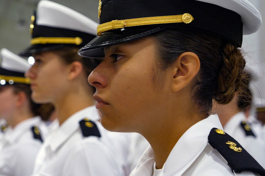 Women in military uniforms stand at attention.