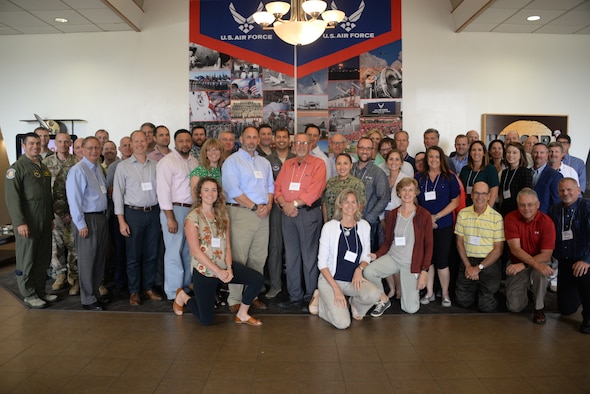 Group of representatives pose for a photo during a meeting to discuss  a variety of topics ranging from improving communication and relationships between wind industry companies, Department of Defense and local communities; technology and more.