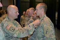 Brig. Gen. David Odonahue, Wisconsin's deputy adjutant general for civil support, pins the Wisconsin National Guard Emergency Service Ribbon on the collars of approximately 150 Wisconsin National Guard Soldiers and Airmen during an Aug. 10, 2019, ceremony at Unity High School in Balsom Lake, Wis. The Guard members helped clear storm debris from more than 50 miles of area roadways in the weeks following strong summer storms July 19.
