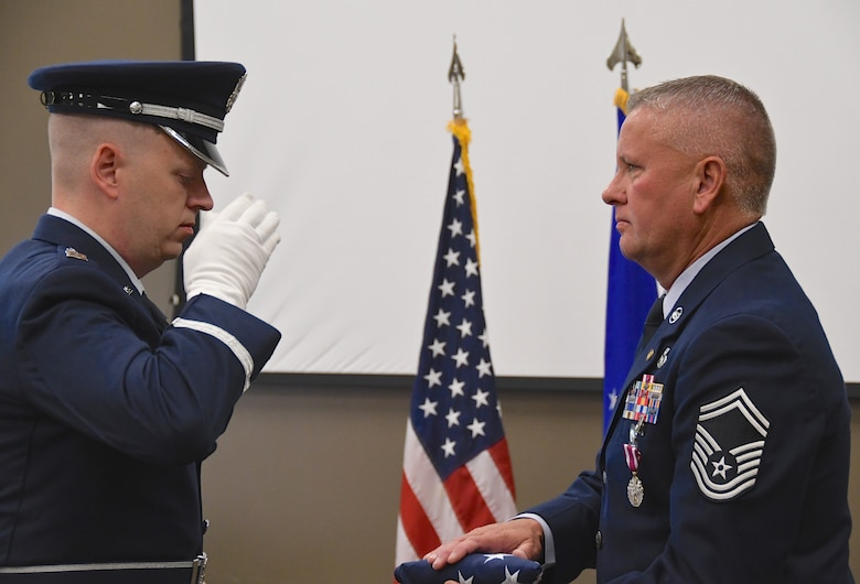 """Senior Master Sgt. William Bassett retired from the 932nd Airlift Wing in a ceremony held August 4, 2019 at Scott Air Force Base, Ill.  Bassett was part of the wing and command post since 2005.  The honor guard presented the American flag to him and a reception with friends and family was held after the singing of the Air Force song. """"Always dream big...always be a good mentor.  It means something.  There are so many friends you meet along the way, but they have no idea how much they impacted your life, and you can impact someone's life too,"""" Bassett said.  (U.S. Air Force photo by Lt. Col. Stan Paregien)"""