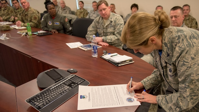 102nd Intelligence Wing commander Col. Virginia I. Gaglio signs declaration as Airmen look on.