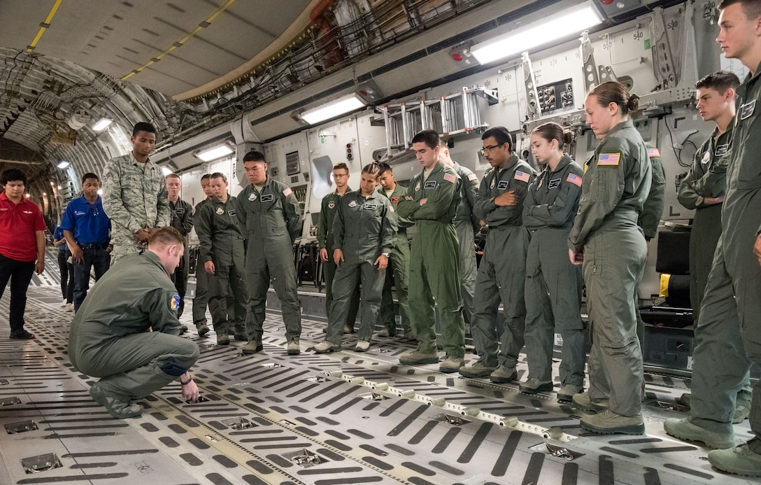 Tech. Sgt. Jordan Rayman, 3rd Airlift Squadron C-17A Globemaster III loadmaster, demonstrates to Air Force Junior Reserve Officers' Training Corps cadets how cargo floor rollers are deployed July 23, 2019, at Dover Air Force Base, Del. Cadets who attended the AFJROTC Summer Flight Academy at Delaware State University in Dover, met with C-17 aircrew members during their half-day tour of the base. (U.S. Air Force photo by Roland Balik)
