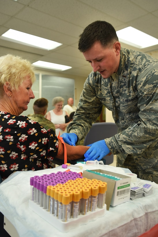 An Airman from the 179th Airlift Wing Medical Group provides medical care as part of GuardCare Weekend Aug. 10, 2019, at the Buckeye Career Center, New Philadelphia, Ohio. GuardCare offers the opportunity for community members to receive basic healthcare and advice on further medical recommendations. (U.S. Air National Guard photo by Senior Airman Gwendalyn Smith)