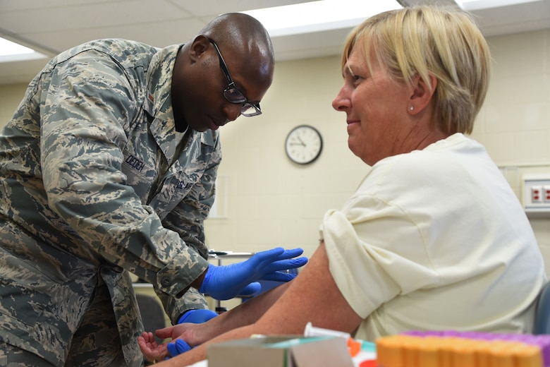 An Airman from the 179th Airlift Wing Medical Group provides medical care as part of GuardCare Weekend at the Buckeye Career Center, New Philadelphia, Ohio, Aug. 10, 2019. GuardCare offers the opportunity for community members to receive basic health care and advice. (U.S. Air National Guard photo by Senior Airman Gwendalyn Smith)