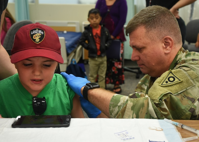 A soldier from the Ohio Army National Guard gives a child an immunization shot as part of GuardCare Weekend Aug. 10, 2019, at the Buckeye Career Center, New Philadelphia, Ohio. During the event both service members from the Ohio Army and Air National Guard provided health services to the local and surrounding New Philadelphia population. (U.S. Air National Guard photo by Senior Airman Gwendalyn Smith)