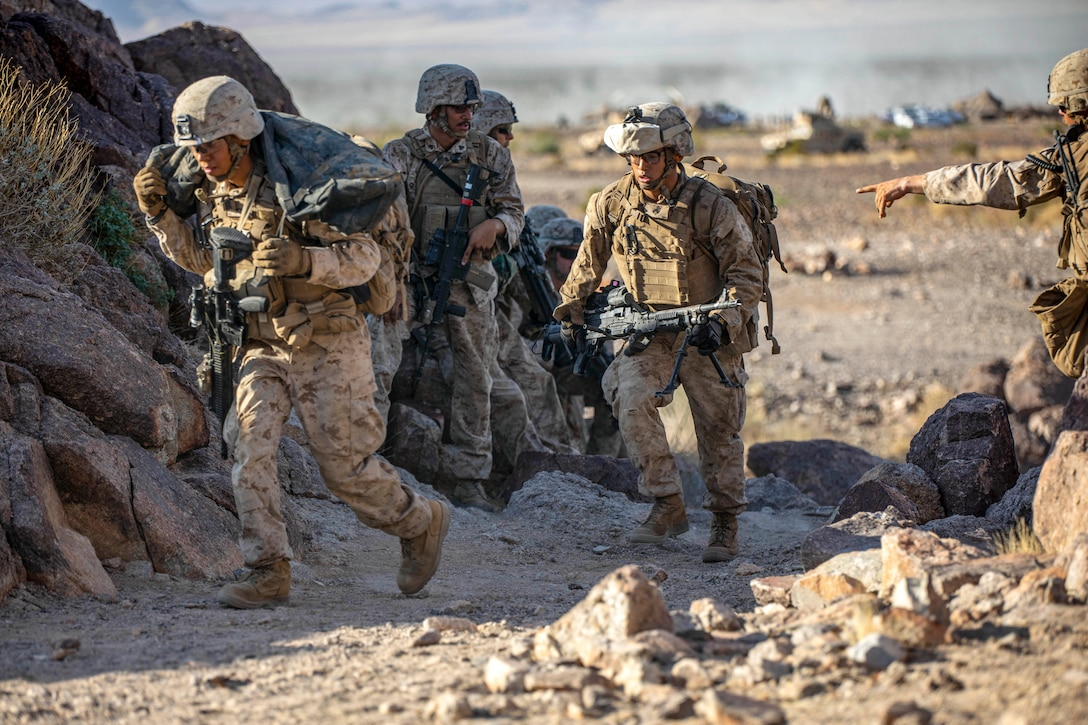 Marines walk with weapons on desert-type terrain.