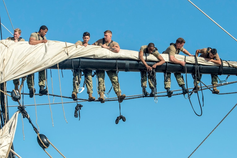 Sailors perched on a horizontal bar on a sailing vessel secure a canvas sail on it.