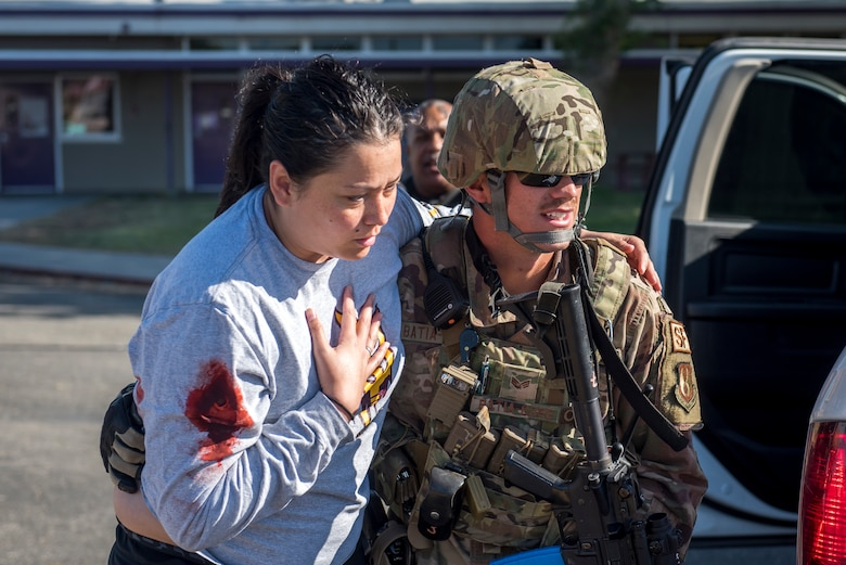 "Senior Airman Timothy Batia-Gore, 412th Security Forces Squadron, escorts a shooting ""victim"" to safety during an active-shooter exercise at Edwards Air Force Base, California, Aug. 9. (U.S. Air Force photo by Richard Gonzales)"