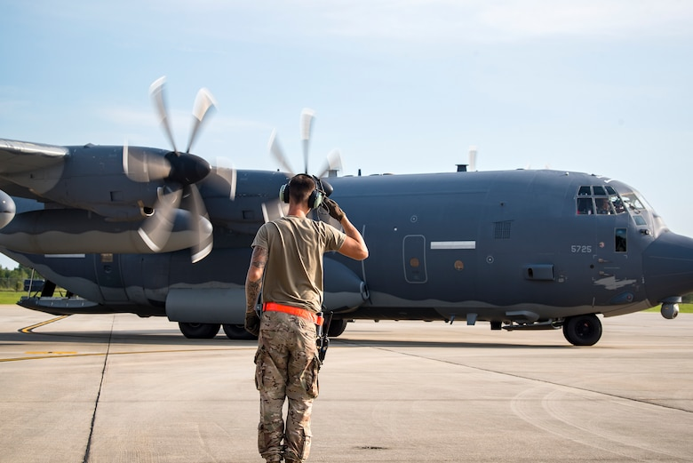 An Airman from the 71st Aircraft Maintenance Unit (AMU), salutes an HC-130J Combat King II prior to takeoff Aug. 13, 2019, at Moody Air Force Base, Ga. Airmen from the 71st AMU perform various tasks prior to takeoff to ensure the aircraft is performing optimally to complete its mission of supporting the 71st Rescue Squadron. Those tasks consist of: pre-flight inspection, removing plugs and cover, repairing any problems found during crew pre-flight checks as well as marshaling the aircraft for takeoff.  (U.S. Air Force photo by Airman 1st Class Eugene Oliver)