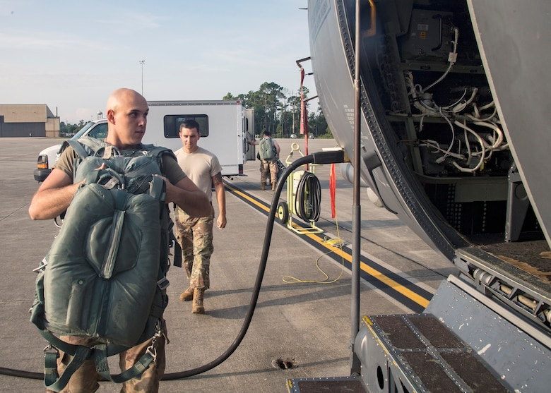 Airman 1st Class Gary Scott, left, 347 Operations Support Squadron aircrew flight equipment (AFE) apprentice, carries AFE onto an HC-130J Combat King II, Aug. 13, 2019, at Moody Air Force Base, Ga. Airmen from the 71st Aircraft Maintenance Unit and other supporting units perform various tasks prior to takeoff to ensure the aircraft is performing optimally to complete its mission of supporting the 71st Rescue Squadron. Those tasks consist of: pre-flight inspection, securing equipment, removing plugs and cover, repairing any problems found during crew pre-flight checks as well as marshaling the aircraft for takeoff. (U.S. Air Force photo by Airman 1st Class Eugene Oliver)
