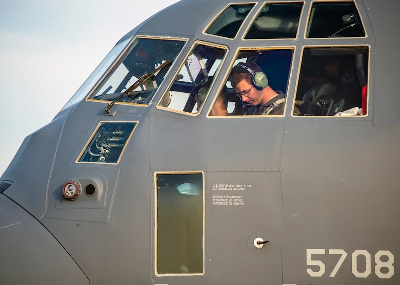 A pilot from the 71st Rescue Squadron (RQS), sits in the cockpit of an HC-130J Combat King II, Aug. 13, 2019, at Moody Air Force Base, Ga. Airmen from the 71st Aircraft Maintenance Unit perform various tasks prior to takeoff to ensure the aircraft is performing optimally to complete its mission of supporting the 71st RQS. Those tasks consist of: pre-flight inspection, removing plugs and cover, fueling the aircraft, repairing any problems found during crew pre-flight checks as well as marshaling the aircraft for takeoff.  (U.S. Air Force photo by Airman 1st Class Eugene Oliver)