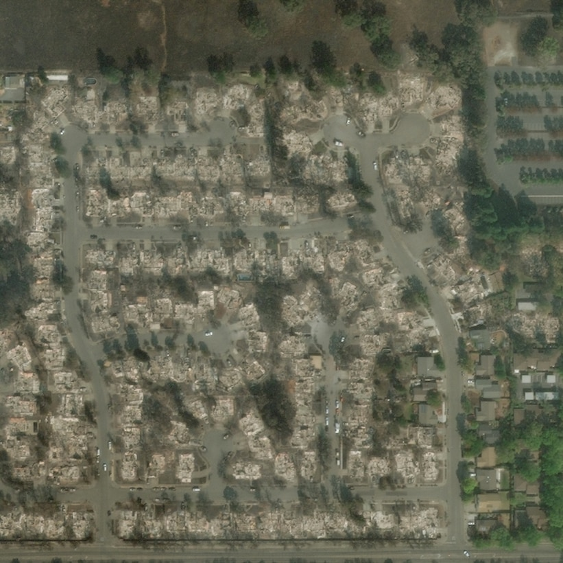 Satellite photo of damaged homes in a residential subdivision.
